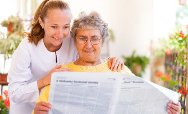 elder woman reading newspaper and staff