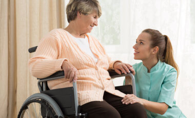 woman on wheelchair and staff smiling