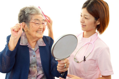 caregiver assisting senior woman taking care of her hair