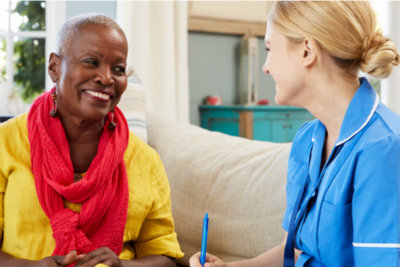 medication support assistance staff talking with the senior woman smiling