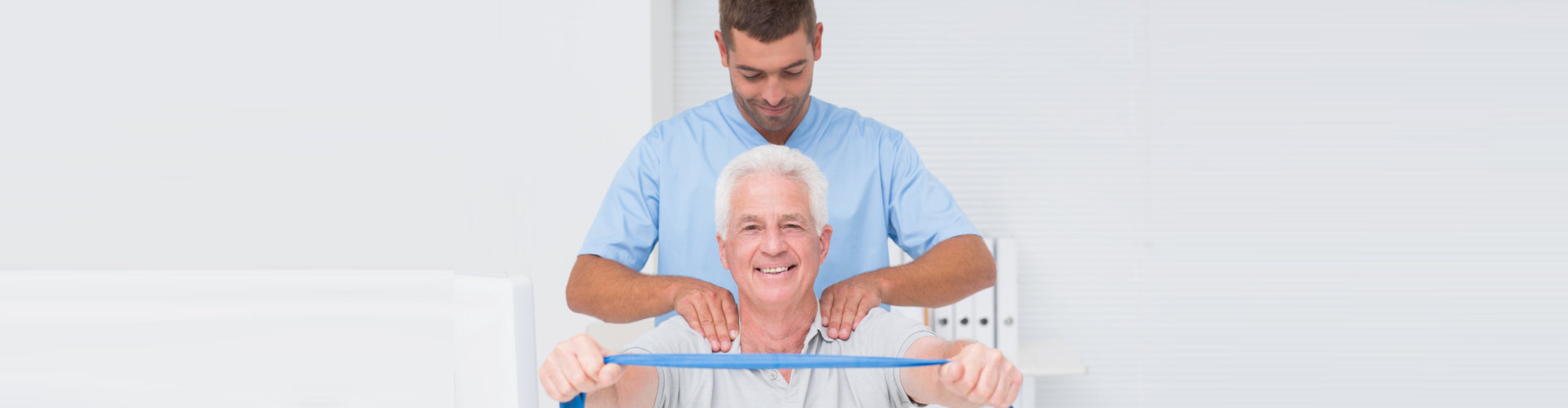 male occupational therapist assisting senior man in exercising with resistance band