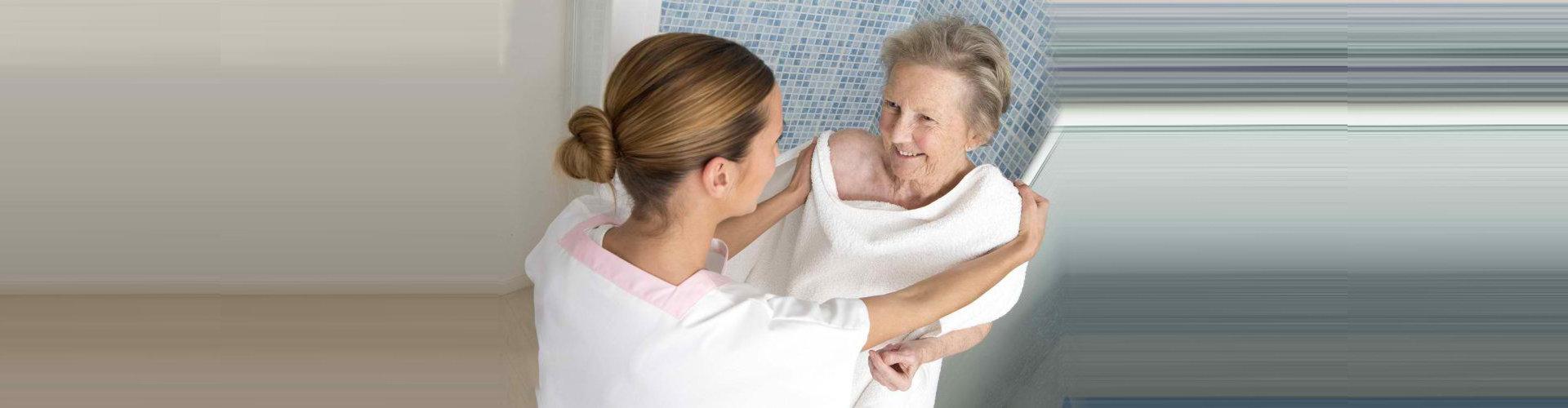 """caregiver assisting a senior woman bathing"