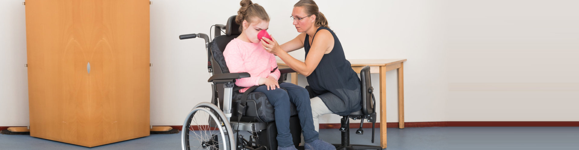 female nurse assisting the little girl in the wheelchair